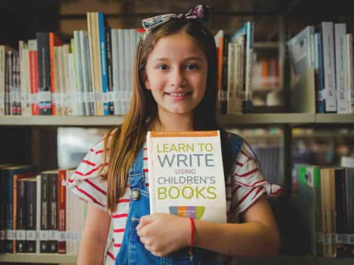 girl holding Learn to Write Using Children's Books